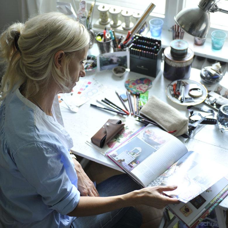 Dagmar BIly sitzt am Schreibtisch und blättert in einem Buch.